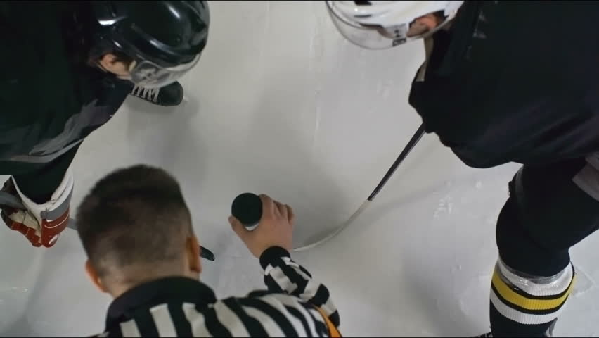 High angle slow motion shot of official dropping a puck during a faceoff