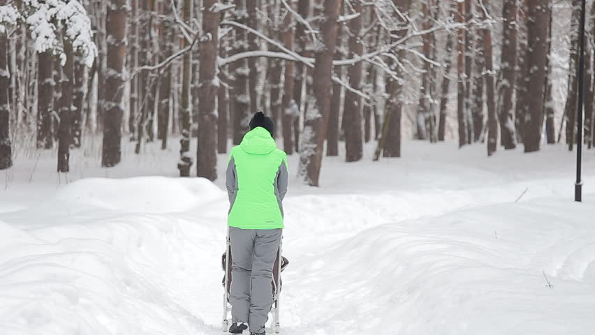 Slow Motion Rear View Of A Young Woman Walking Alone Through Snow Blizzard In Park Stock Footage