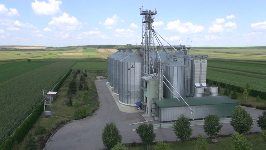 Agricultural silos in the fields. Blue sky with white clouds.