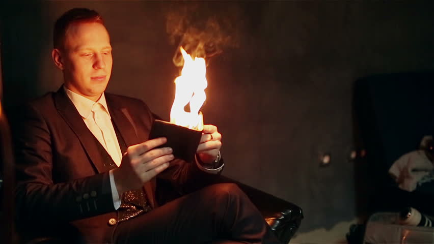 The flame is illuminating the face of the conjurer. Magician is holding a burning purse in his hand.