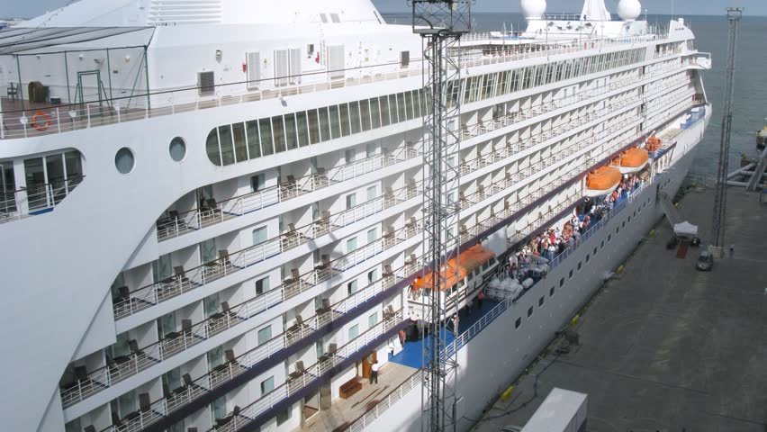 Enormous cruise liner stationed at bay, top-down view, time lapse
