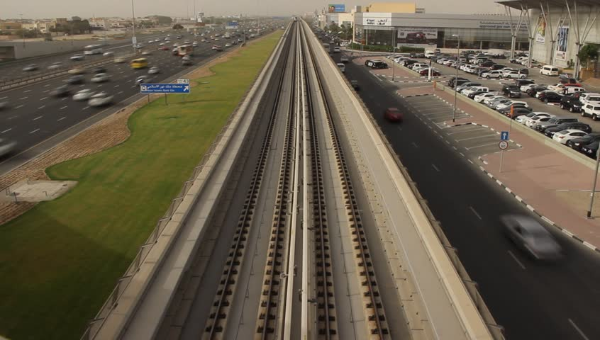 Elevated Dubai Metro railway, Red line. Train quickly approach and pass under, view from above, time lapse shot. Inter-city highway Sheikh Zayed road at left side, car parking, Al Quoz area on right
