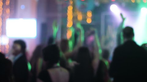 Blurred footage of crowded hall at night club with dancing young people around  students hanging out at their prom night, young people are celebrating wedding.