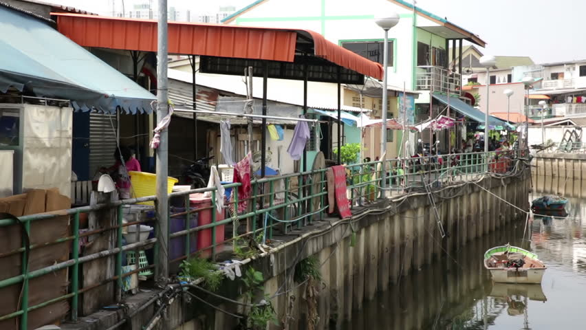 PATTAYA THAILAND CIRCA MARCH 2015 Girl Moves Bicycle Motorcyclist Passes Through Riverside Alleyway
