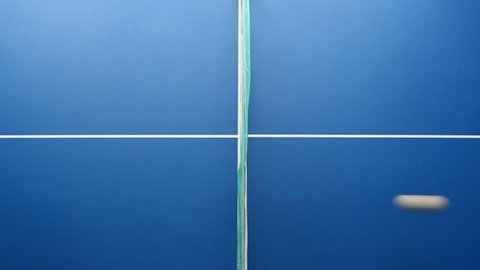 Table tennis or ping pong ball, net and blue table above close up view