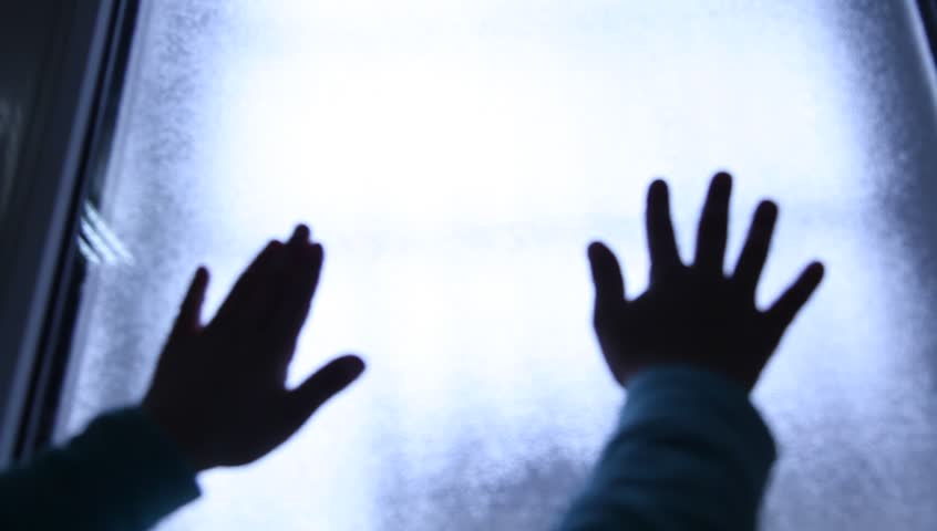 Helpless Child seeking exit and begging for help. Escape. Silhouette of children hands on the light window. Refugees or abandoned child. Mental Institution. Family violence. Fingers on the glass