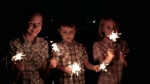 Happy kids standing on the road and burning sparkles at the night time. Concept Brother and Sister Together Forever