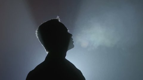The man look up against a background of bright light. Evening-night time, foggy weather, real time capture