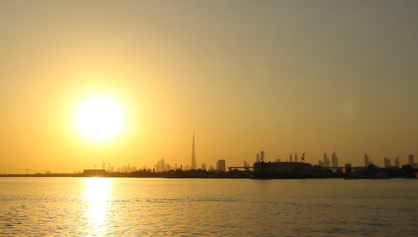 Dubai sunset, Creek Harbour water, golden low sun glow ahead, cityscape silhouette, tall towers stand in line far away. Darker overground Creek Station, end of green line, unused part
