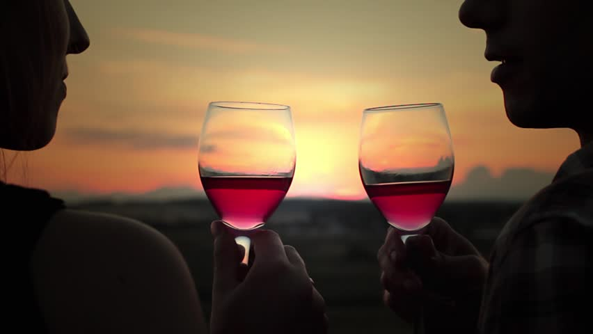 Young happy couple in love kissing and drink wine at sunset