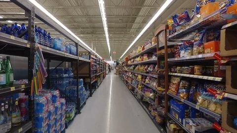 MONTREAL, CANADA - FEBRUARY 2016: Slow Motion: Walking through Walmart aisle (Chips, snacks, soda drinks & fast food)