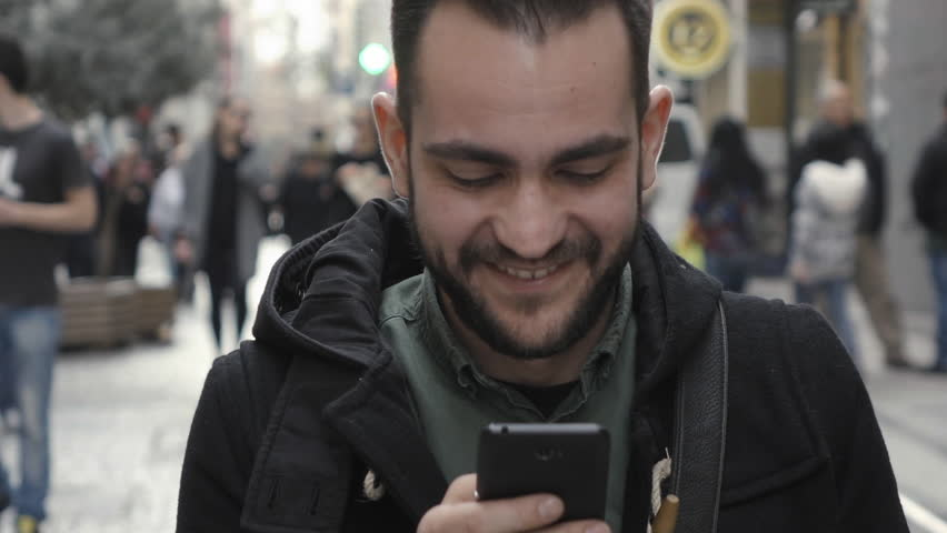Young man using smartphone in public commercial street slomo.100p slow motion clip of a young man in casual war using a smartphone in the middle of a commercial street surrounded by shops and people