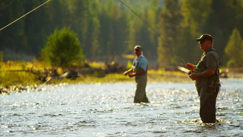 Canadian males fly fishing in competition on freshwater river