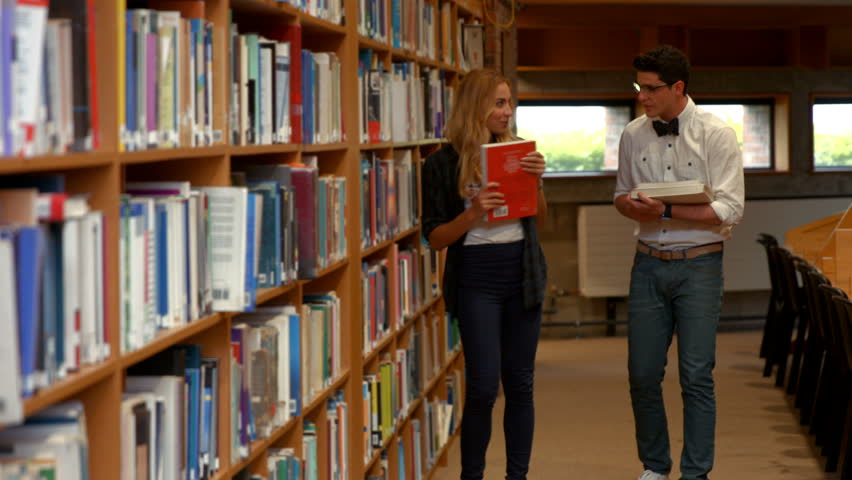 Pretty student talking to nerd in library at the college | Shutterstock HD Video #14714638