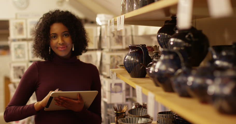Young woman inspecting quality of the ceramics in her shop.