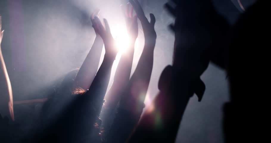 Slow mortion shot of young festive people with their hands raised and in the air at concert or party. Smoke is lingering in the nightclub and silhouettes of teenagers dancing. #14730802