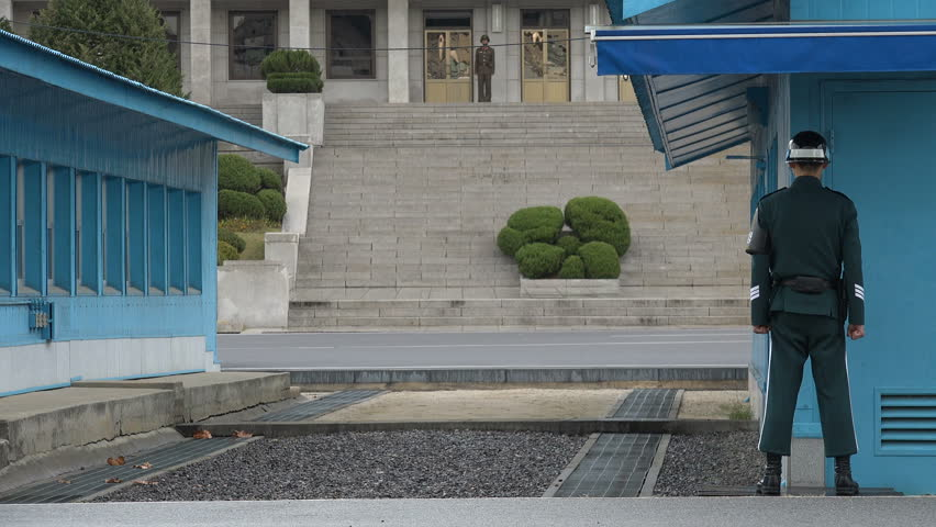 DMZ, SOUTH KOREA - 10 OCTOBER 2015: A South Korean soldier stands guard at the UN buildings at Panmunjom, keeping an eye on their counterparts of the North at the official demarcation line