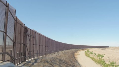 Pan shot of the US and Mexico border fence from one side to the other in 4K on a sunny day.