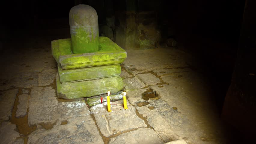 Candles on the stone floor of a Hindu temple. in front of a Lingam and Yoni. symbols of the god Shiva and the goddess Shakti. Video UltraHD
