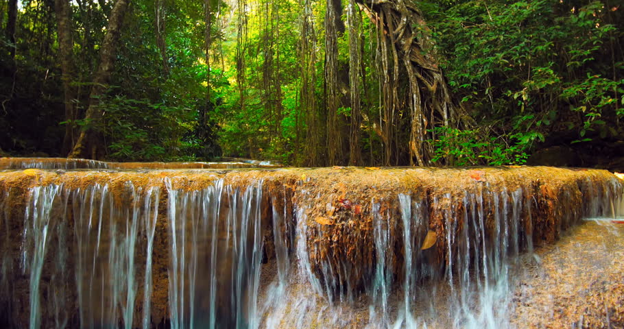 Slider video shot of waterfall cascade on river flowing through jungle forest