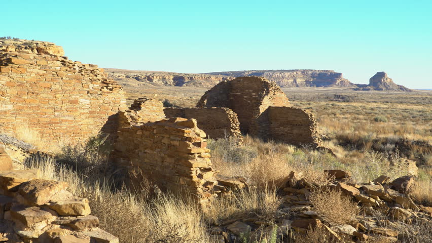 Tracking shot with pan left motion of exterior of Pueblo Bonito ruin at Chaco Culture National Historic Park in New Mexico
