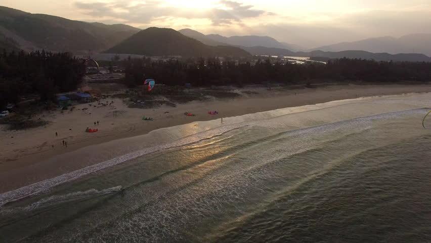 Kite surfer surfing at the beach in Sanya, Hainan island, China during sunset