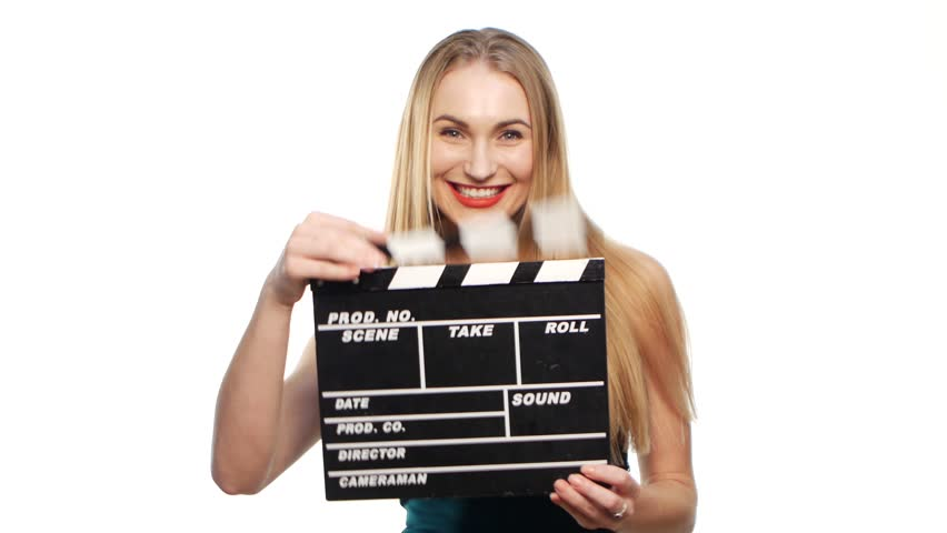 Elegant woman with sexy red lips go, using clapper board and smiling, on white