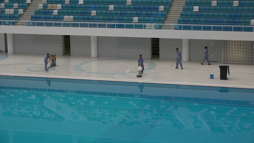 BEIJING, CHINA   14 SEPTEMBER 2015: Workers Clean The Swimming Pool In The  Water