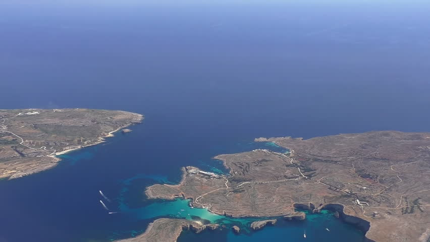 Aerial view of Malta Comino island with turquoise crystal clear water of Blue Lagoon between Comino and islet of Cominotto.Establishing shot .
