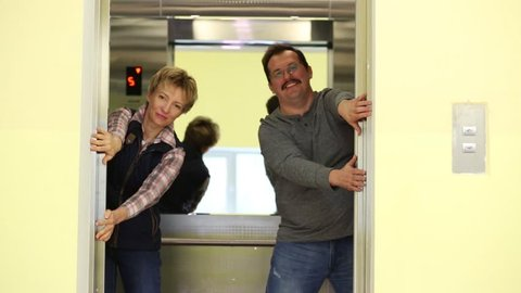 A man and a woman substituting hands and prevent the elevator doors closed