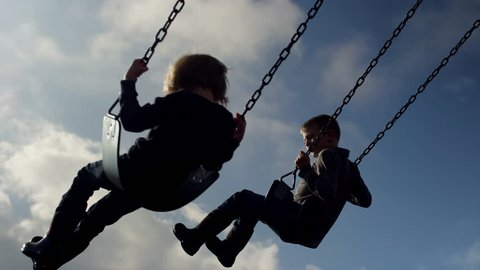Siblings swinging in time together, slow motion, silhouette in the sky