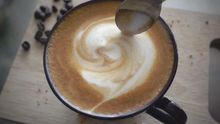 Stiring milk foam in a cup of latte coffee, slow motion  #14936788