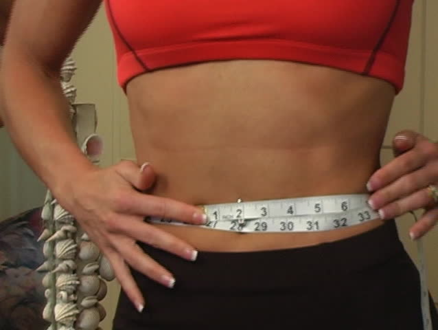 Close-up of a woman's waist with remarkable muscle definition, facing the camera.  She places a measuring tape around her waist and turns to a mirror.