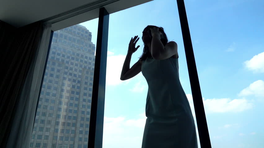 Angry businesswoman talking on cellphone by window in the office, super slow motion
