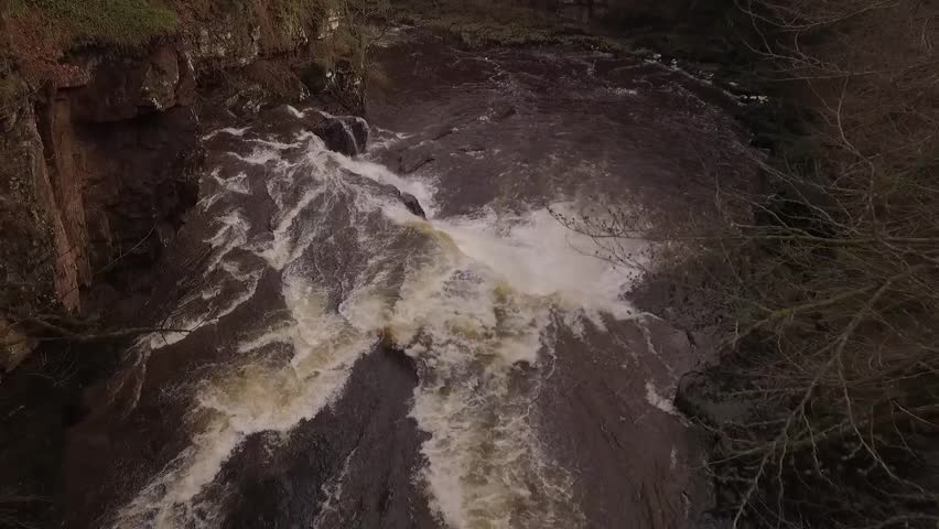 Aerial reverse flyover of a heavy flowing waterfall in Scotland.