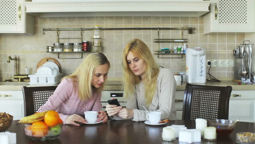 Two Girls Looking At Mobile Phone While Sitting At A Table With Tea In The  Kitchen