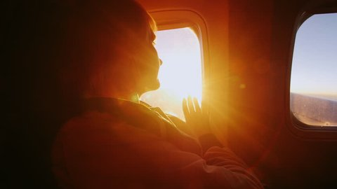 Young woman looking at the sun from the window of an airliner. It touches the rays of the sun. Concept - touch the dream, the perfect trip and vacation