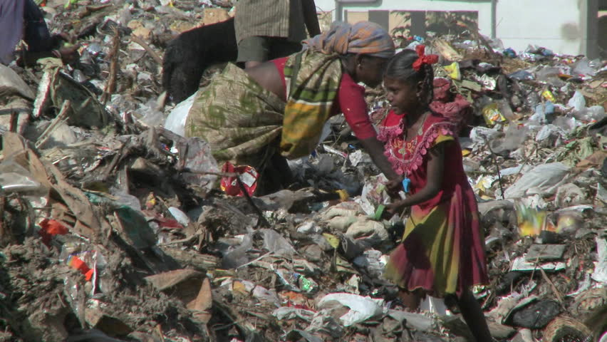 INDIA - CIRCA 2010: People scavenge through rubbish circa 2010 in India.  There are about 150,000 Kabaris (people in India who collect and sell recyclable materials) total in Delhi who recycle about 59% of the city's waste to support themselves and thei