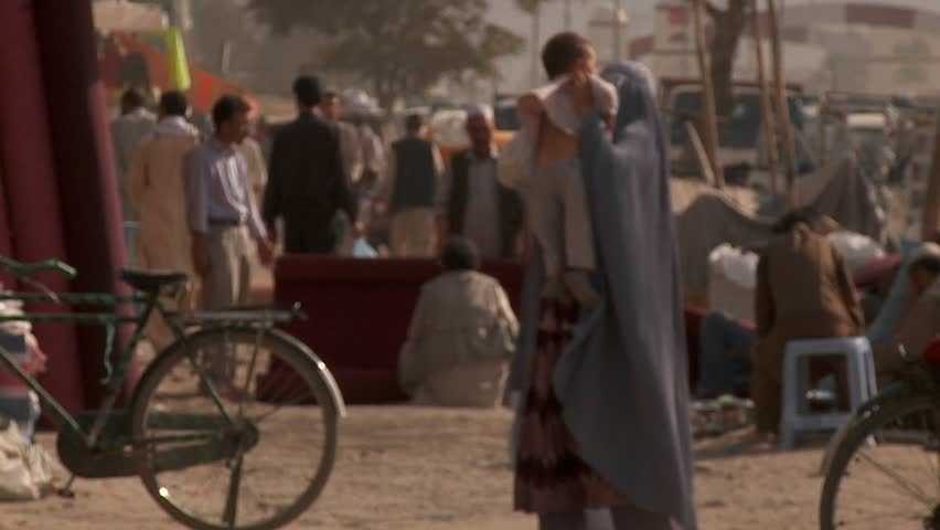 KABUL, AFGHANISTAN - CIRCA 2009: Slow-motion shot of a woman in burka walking with her child circa 2009 in Kabul, Afghanistan. The official religion in Afghanistan is Islam, which is practiced by over 99% of its citizens.