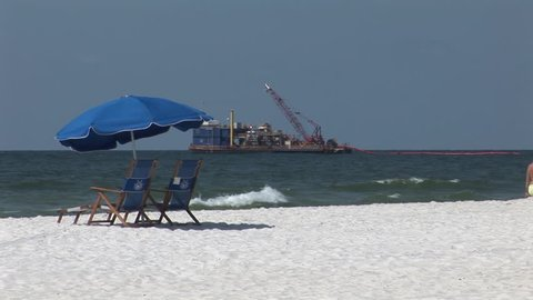 A ship lays out an oil boom to protect the beach after the BP Oil Spill in the Gulf of Mexico