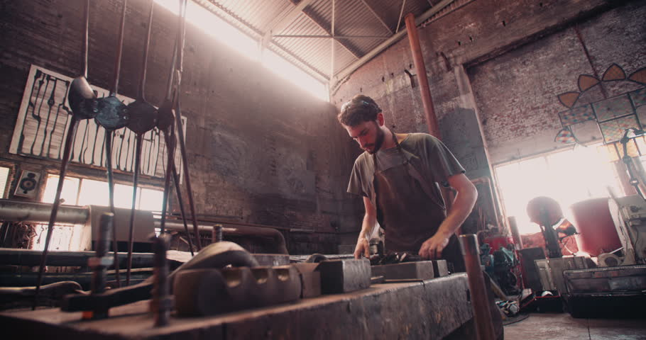 Young adult man working on a blacksmith shop showing great concentration on his job
