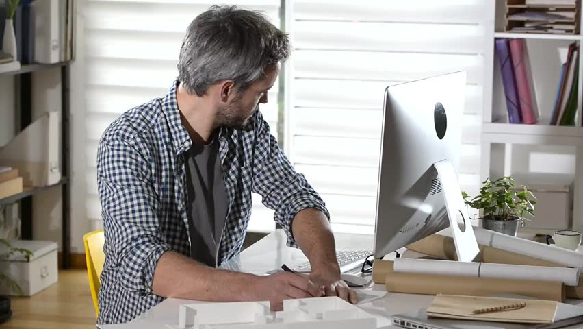 Mixed race architect in design agency working with blueprint an architect sitting at his desk and working on a building project hd stock footage malvernweather Images