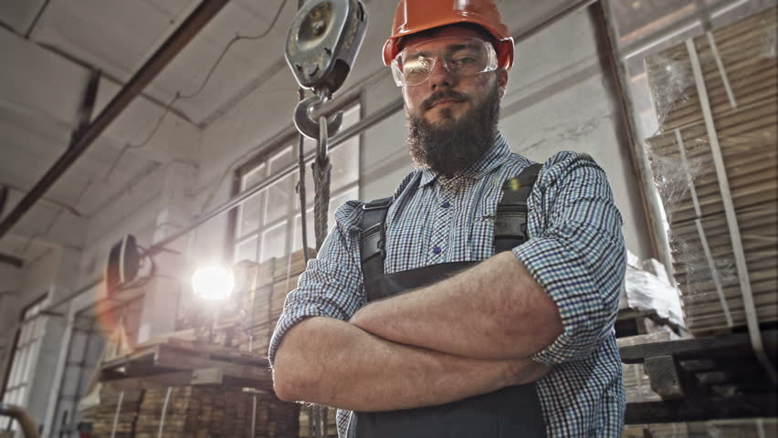 Bearded industrial worker in protective helmet and goggles at the steel timber crane in a warehouse. RAW video record.