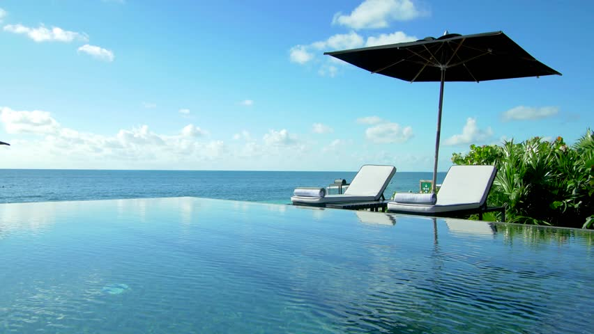 Lounge Chairs in tropical paradise over infinity pool