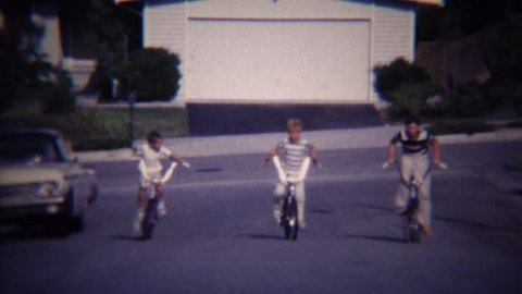 LOMITA, CALIFORNIA 1972: 3 caucasian kids riding bikes uphill on residential suburban street.