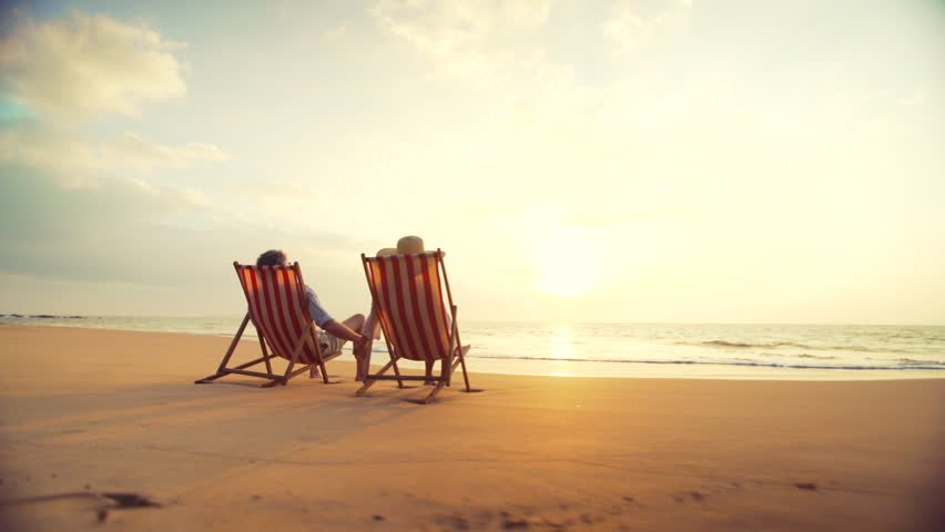 4K Retirement Vacation Concept, Happy Mature Retired Couple Enjoying Beautiful Sunset at the Beach