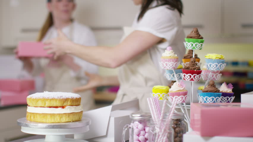 4k female business partners in home bakery business packing cakes in boxes 4k stock video