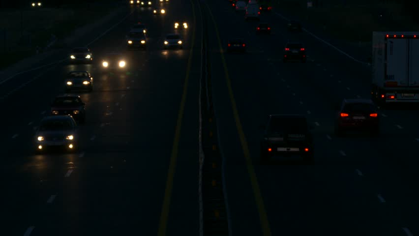 Ungraded: Highway at Night / Highway Road / Highway Traffic. Cars driving on a six-lane highway with head-lights turned on. Source: Lumix DMC, ungraded H.264 from camera. (av25733u)