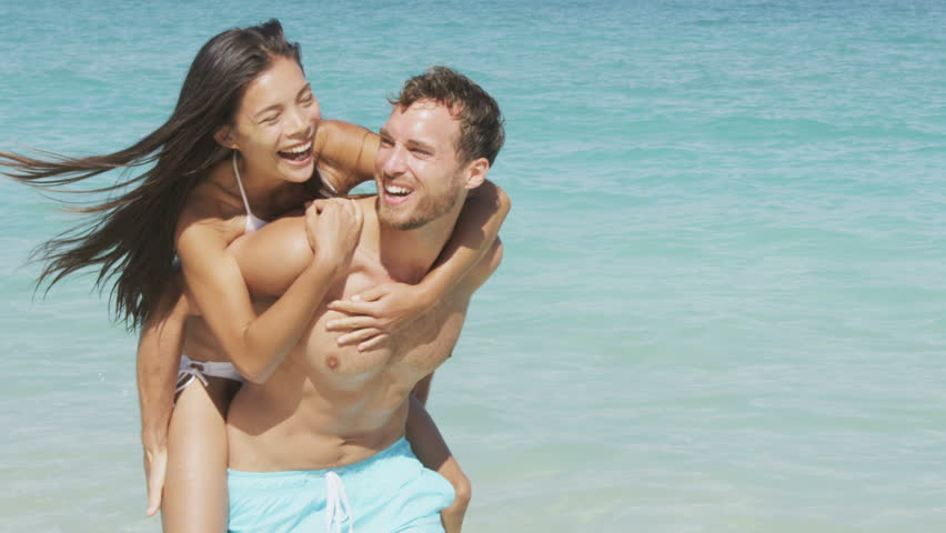 Couple beach vacation fun. happy young people in love doing piggyback. Mixed race asian chinese woman piggybacking on the back of Caucasian man laughing in love during summer holidays or vacations.