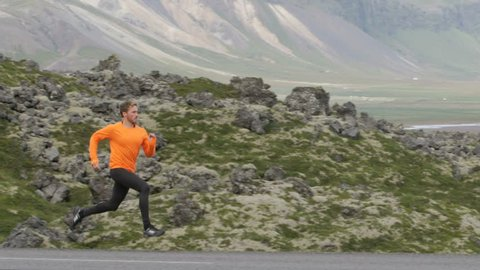 Running sport man sprinting in slow motion on mountain road. Male runner exercising and training outdoors in beautiful mountains nature landscape on Iceland.
